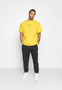 Karl Kani - SMALL SIGNATURE PINSTRIPE TEE UNISEX - Print T-shirt - yellow/white - 1