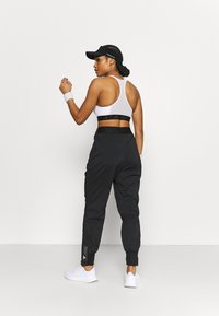 adidas Performance - Tracksuit bottoms - black - 2