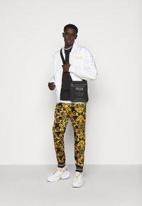 Versace Jeans Couture - TECNO  PRINT LOGO BAROQU  - Tracksuit bottoms - black - 1