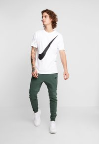 Nike Sportswear - Spodnie treningowe - galactic jade/black - 1