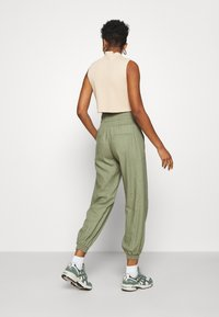 ONLY - ONLPALMA  MIX TRACK  - Tracksuit bottoms - oil green - 2