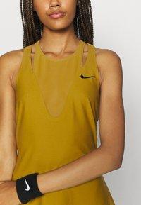 Nike Performance - MARIA DRESS - Sports dress - ochre/black - 6