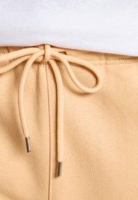 9N1M SENSE - LOGO PANTS UNISEX - Trousers - pantone apricot - 4
