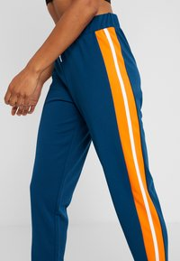 ONLY Play - ONPTANGERINE LOOSE TRACK PANTS - Pantalones deportivos - gibraltar sea/celosia orange - 4