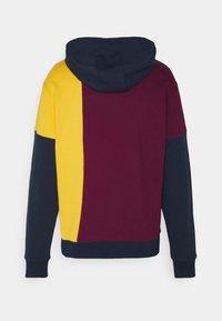 New Balance - NB ATHLETICS HIGHER LEARNING HOODIE - Sweatshirt - red/dark blue/yellow - 1