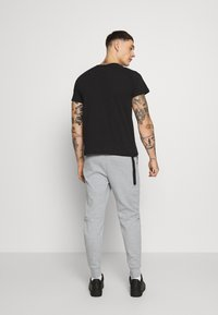 Nike Sportswear - Tracksuit bottoms - grey heather/black - 2