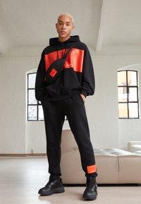 Calvin Klein Jeans - OVERSIZED LARGE BADGE HOODIE UNISEX - Sweatshirt - black - 1