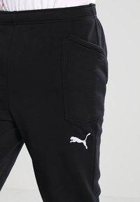Puma - LIGA CASUALS PANTS - Pantalon de survêtement - black/white - 3