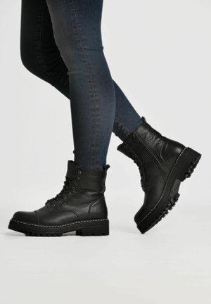 KATHI  - Lace-up ankle boots - black/ white