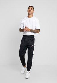 Nike Sportswear - TEARAWAY  - Tracksuit bottoms - black/white - 1