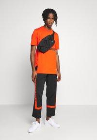 adidas Originals - WARMUP - Tracksuit bottoms - black/corang - 1
