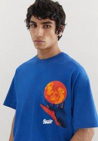 PULL&BEAR - MIT KUGEL UND WÄRMEKARTE - Print T-shirt - blue - 3