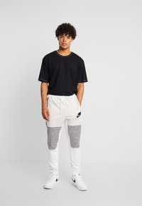Nike Sportswear - PANT BODYMAP - Tracksuit bottoms - light bone/summit white/black - 1