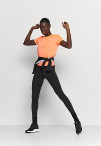 Nike Performance - MILER - T-shirt med print - bright mango/silver - 1