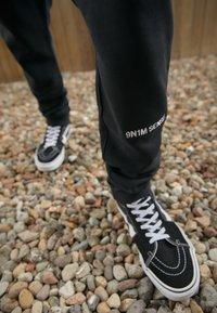 9N1M SENSE - LOGO PANTS UNISEX - Tracksuit bottoms - black - 2