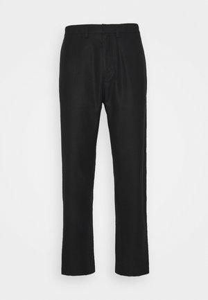 TAREK - Trousers - black