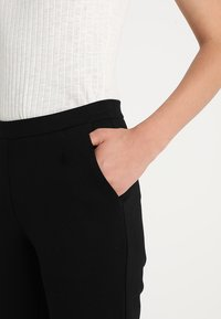 Modström - TANNY FLARE PANTS - Trousers - black - 4