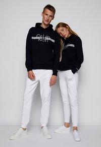 Calvin Klein - REFLECTIVE CHEST STRIPE HOODIE UNISEX - Sweatshirt - black - 3