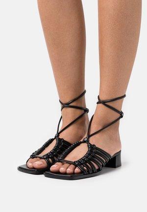 RIKA - Sandals - black