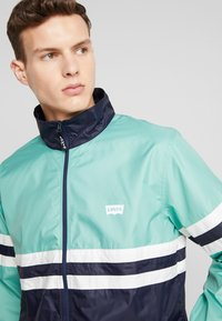 Levi's® - COLORBLOCKED WINDBREAKER - Summer jacket - night blue/crème/menthe - 3