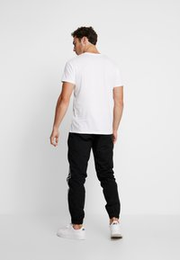 Calvin Klein Jeans - SIDE STRIPE TRACK PANT - Tracksuit bottoms - black - 2
