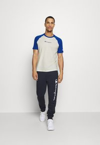 Champion - LEGACY CREWNECK  - T-shirt med print - off-white/blue - 1