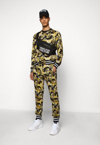 Versace Jeans Couture - FLEECE NEW LOGO - Tracksuit bottoms - nero - 1