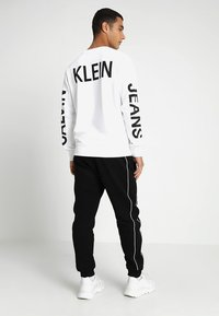 Calvin Klein - LOGO PRINT - Pantalon de survêtement - perfect black