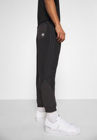 adidas Originals - UNISEX - Tracksuit bottoms - black - 3