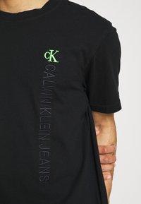Calvin Klein Jeans - WASHED INSTITTEE UNISEX - Print T-shirt - black - 4