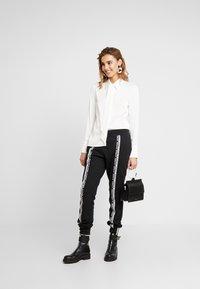 adidas Originals - R.Y.V. CUFFED SPORT PANTS - Verryttelyhousut - black - 1