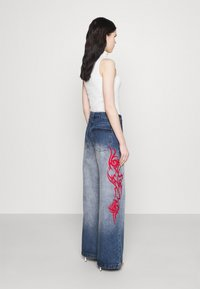 Jaded London - SKATER FIT TRIBAL PLACEMENT - Flared jeans - blue/ red - 2