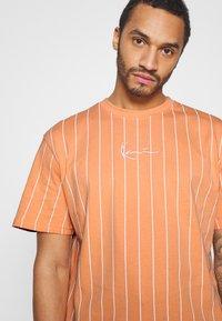 Karl Kani - SMALL SIGNATURE PINSTRIPE TEE UNISEX - Print T-shirt - coral/white - 5