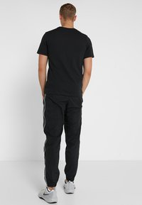 Nike Performance - TEE CREW SOLID - T-shirts - black/white