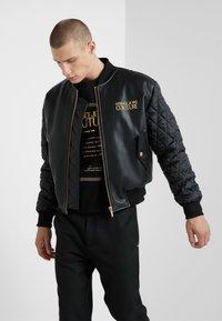 Versace Jeans Couture - GIUBBETTI UOMO - Giubbotto Bomber - nero - 0