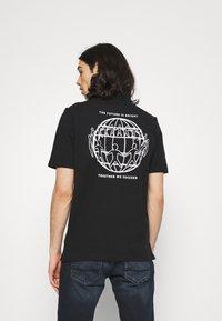 Tommy Hilfiger - ONE PLANET BACK LOGO UNISEX - Polo shirt - black - 2
