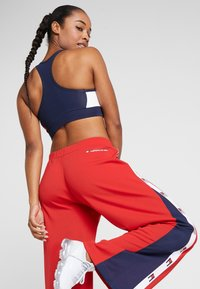 Tommy Sport - FLAG TAPE PANT FLARE - Träningsbyxor - red - 4