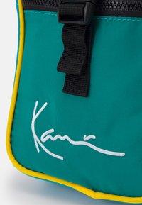Karl Kani - SIGNATURE BLOCK MESSENGER BAG UNISEX - Taška spříčným popruhem - green - 3