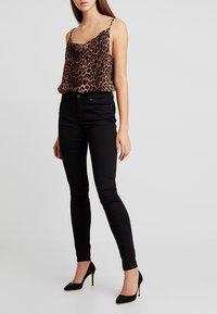 Vero Moda - VMHOT SEVEN SLIM PUSH UP PANTS - Trousers - black - 0