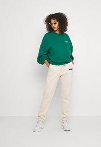 Nly by Nelly - EMPOWERED PANTS - Teplákové kalhoty - creme - 1