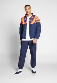 adidas Originals - FOOTBALL GRAPHIC TRACK PANTS - Tracksuit bottoms - blue - 1