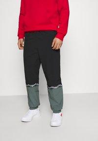 adidas Originals - SLICE TREFOIL ADICOLOR PRIMEGREEN ORIGINALS SLIM TRACK - Tracksuit bottoms - black/blue oxide - 0
