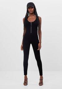 Bershka - MIT GESMOKTEM AUSSCHNITT - Jumpsuit - black - 1