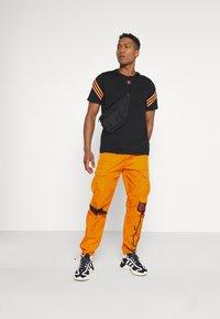 Karl Kani - SIGNATURE CRINCLE PANTS UNISEX - Pantalon cargo - orange - 1