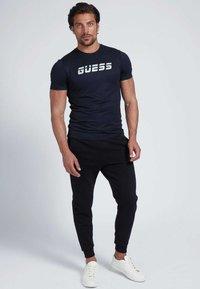Guess - Tracksuit bottoms - schwarz - 1