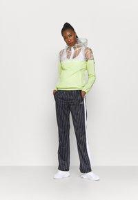 Fila - JAIMI PINSTRIPE TRACK PANTS - Teplákové kalhoty - black/bright white - 1