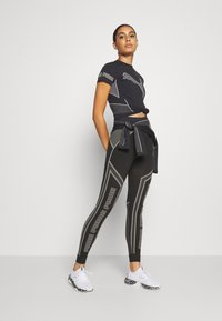 Puma - EVOSTRIPE EVOKNIT - Leggings - black - 1
