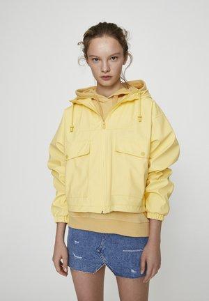 MIT KAPUZE UND TASCHEN - Vodotěsná bunda - yellow