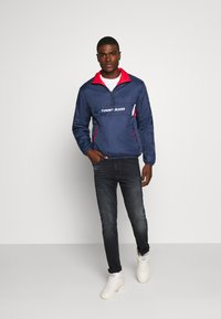 Tommy Jeans - REVERSIBLE RETRO POPOVER - Light jacket - twilight navy - 1