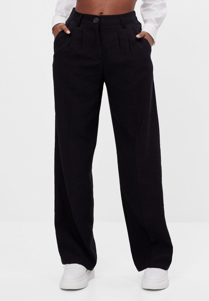 Bershka - MIT WEITEM BEIN - Trousers - black